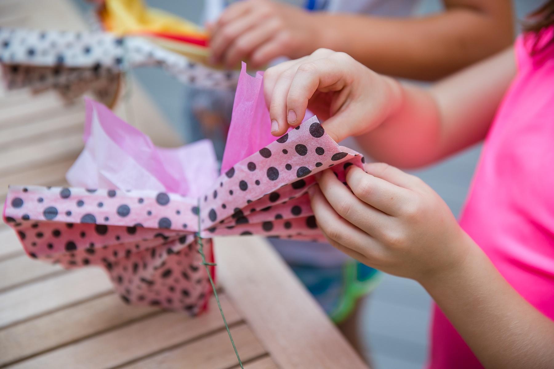 Kids' hands shown making tissue paper flowers
